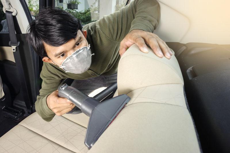 戴口罩的男人用吸尘器清洗他的汽车