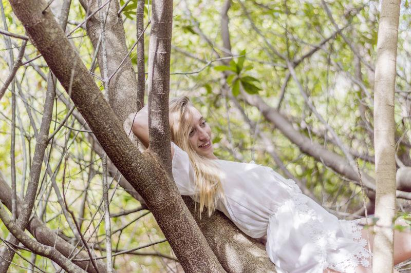 躺在树枝上微笑的美女