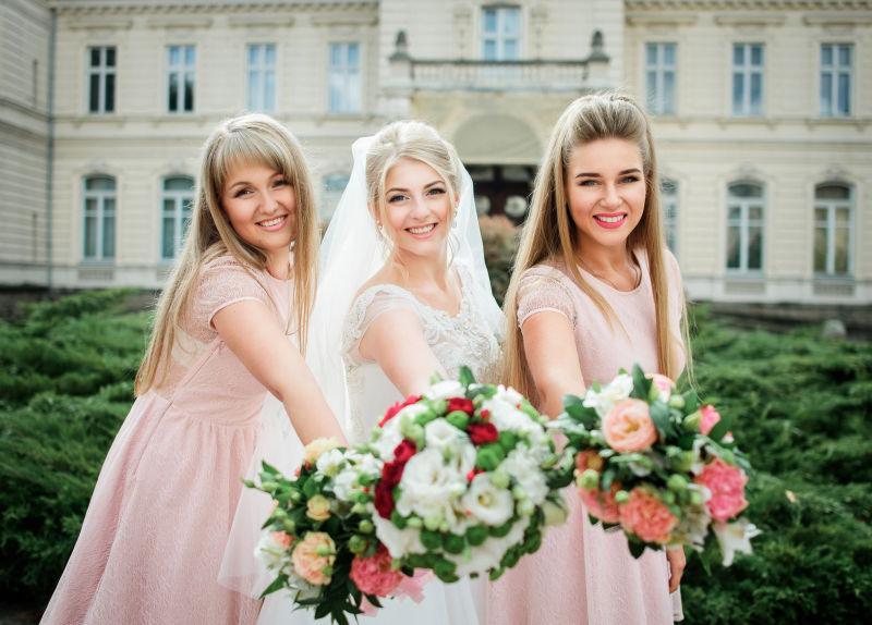 伴娘穿着粉色衣服和新娘双手捧着结婚花束
