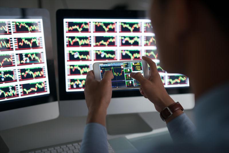 商人拿手机分析对比股票市场行情