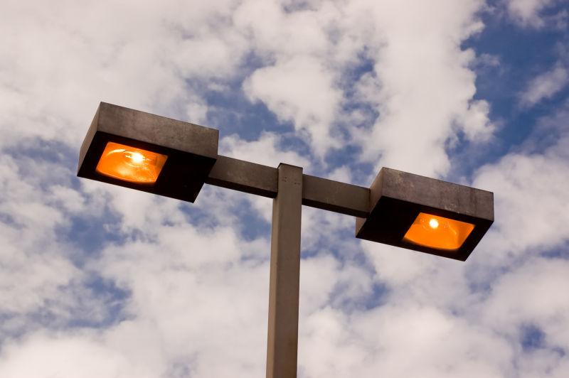 蓝天白云下亮着的路灯