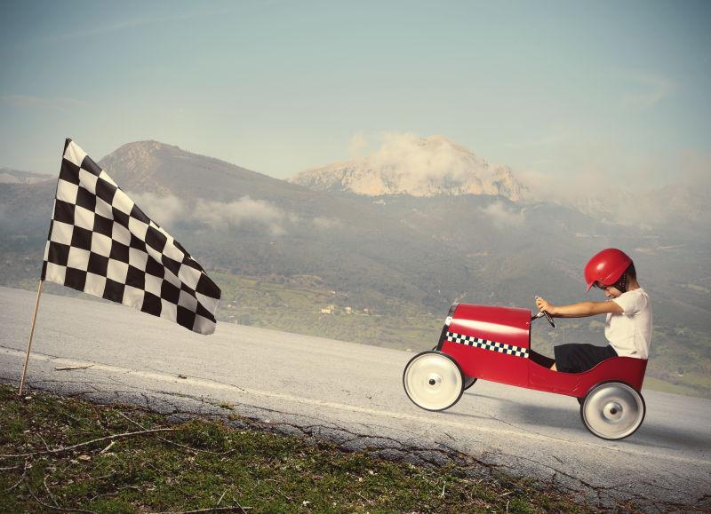 孩子用一辆小汽车爬山去拿旗子
