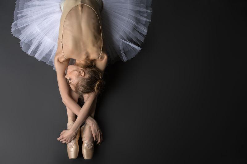 优雅的芭蕾舞演员坐在地板上