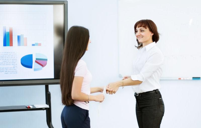 办公室里的两个握手的美女