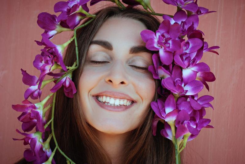 紫色兰花包围的美丽微笑的女孩