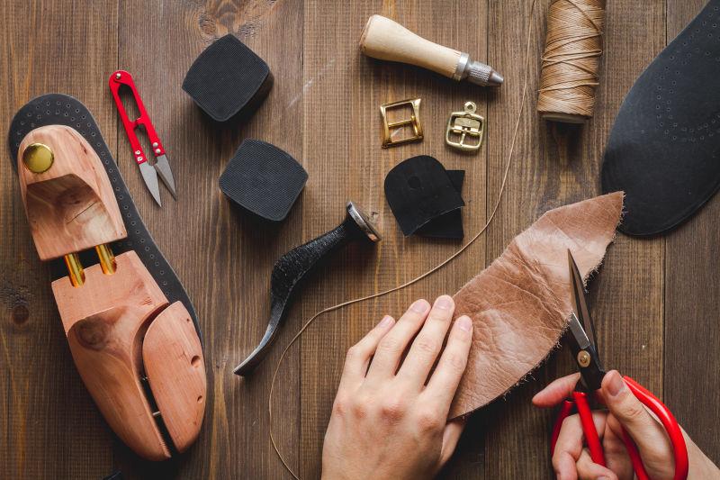 正在木桌上做鞋子的人