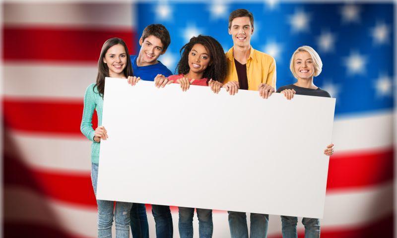 美国国旗背景下年轻人拿着白色纸板