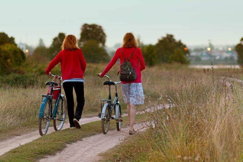 骑自行车的两个穿红色衣服的女性