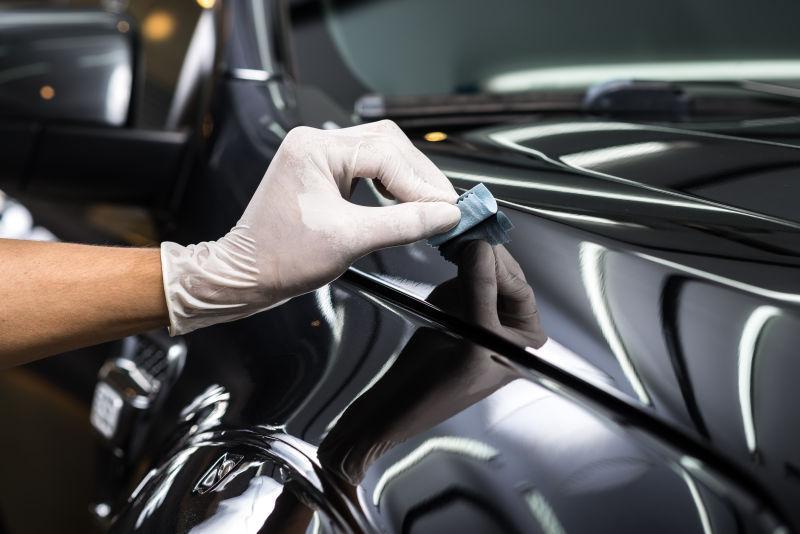 戴着手套拿抹布擦拭黑色汽车的工人