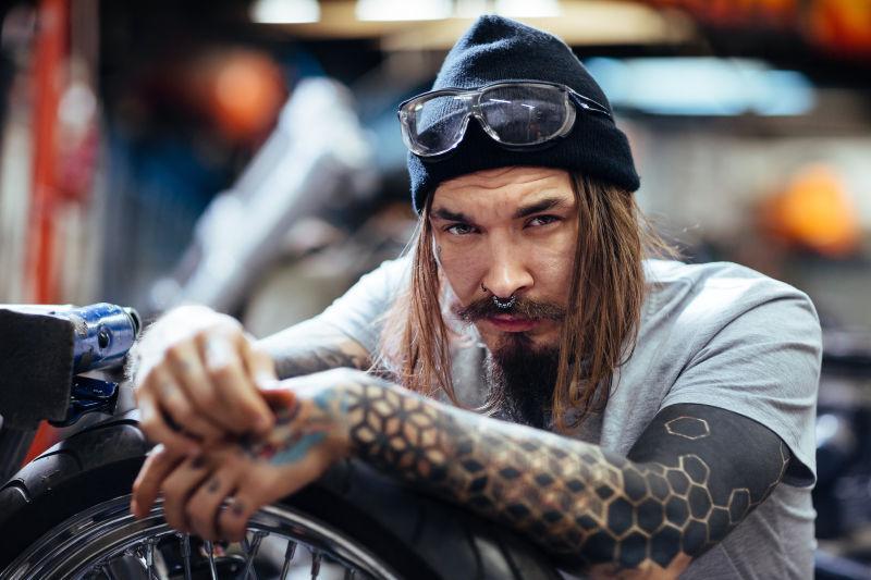 戴着帽子的有胡子的男人和他的自行车