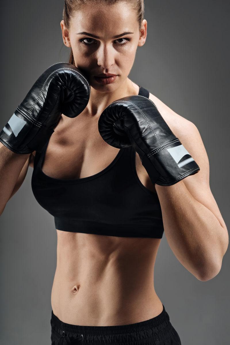 灰色背景下戴着拳击手套打拳的美女