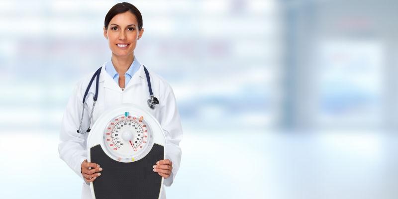 拿着秤带着听诊器的微笑的女医生