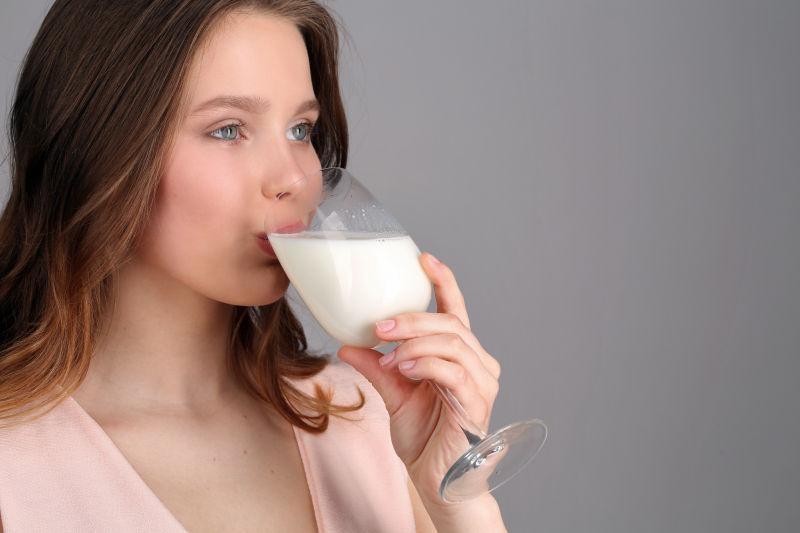 穿着粉红色的衬衫的女孩喝着牛奶