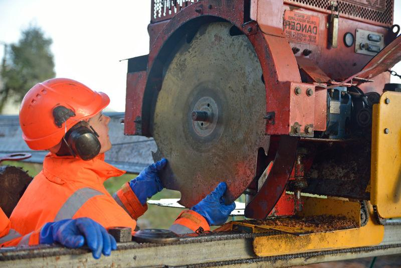 工作人员给锯木厂的机器更换刀片
