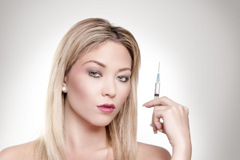 拿着注射器的美丽的女人肖像