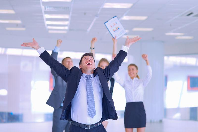 双手抛向天空庆祝胜利的业务团队