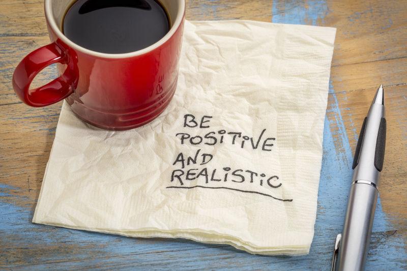 用餐巾纸书写积极向上和一杯咖啡