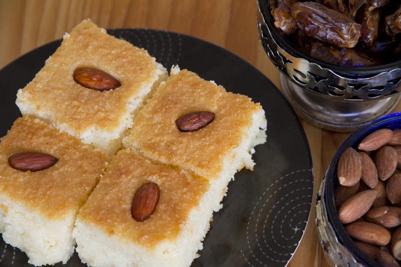 木桌上放在餐盘里的放着杏仁的美味的甜点