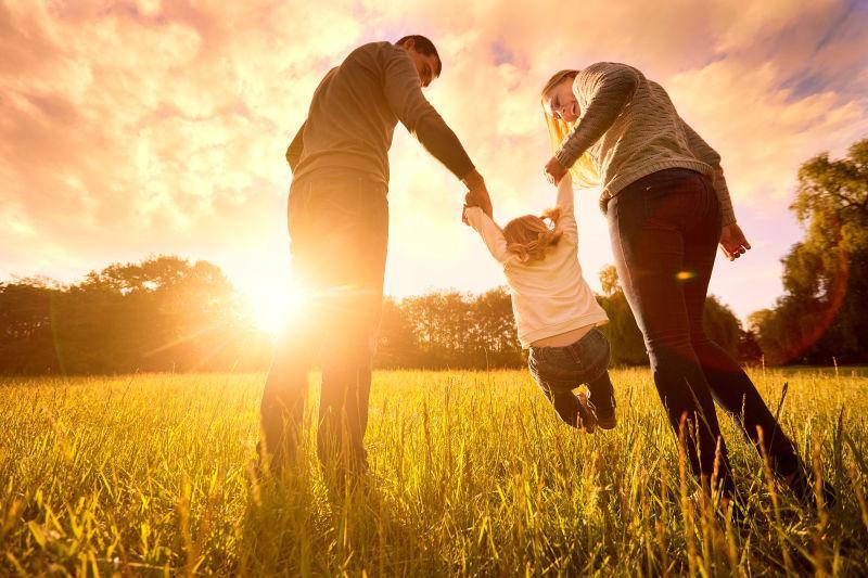 草地上父母牵着婴儿的手