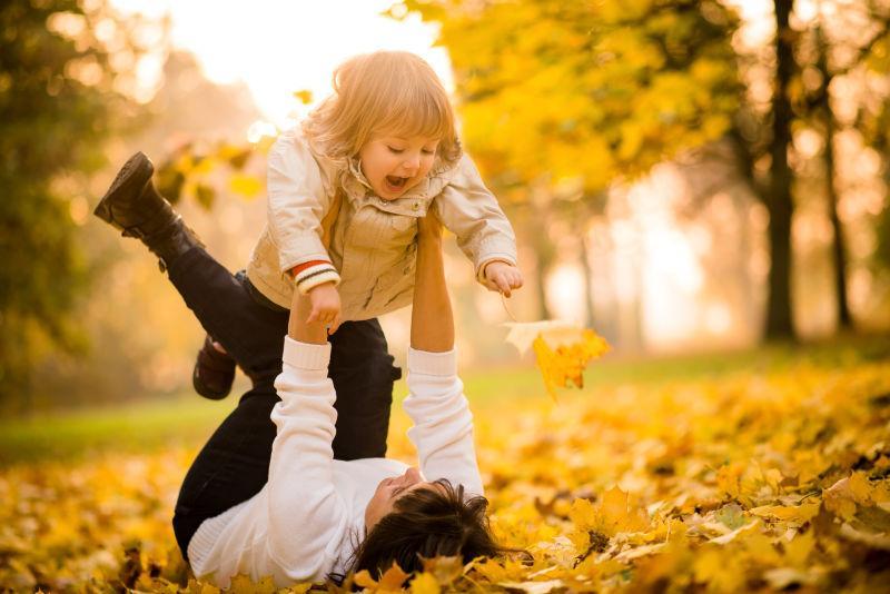 母亲和孩子在秋天的大自然里