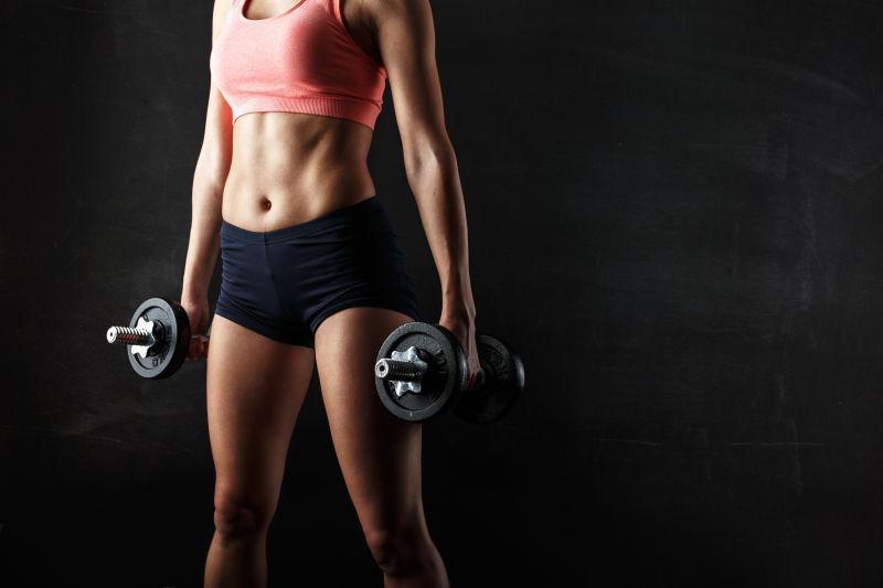 黑色背景中肌肉健身的女子