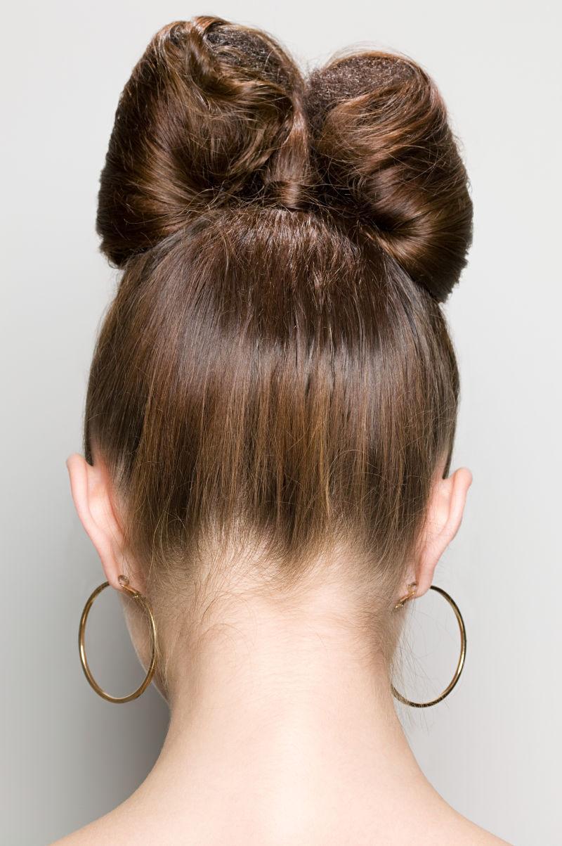 精美发型的戴耳环的美女后视图