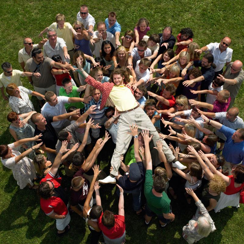草地上被人群托起来的男人