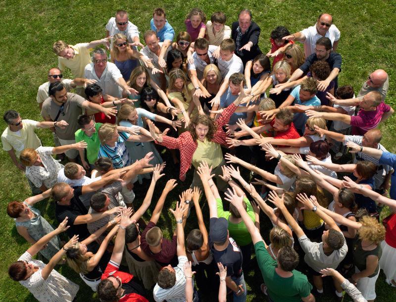 草地上被人群围在中心的男人