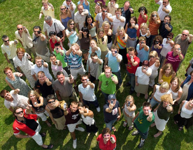 草地上拿着手机的人群