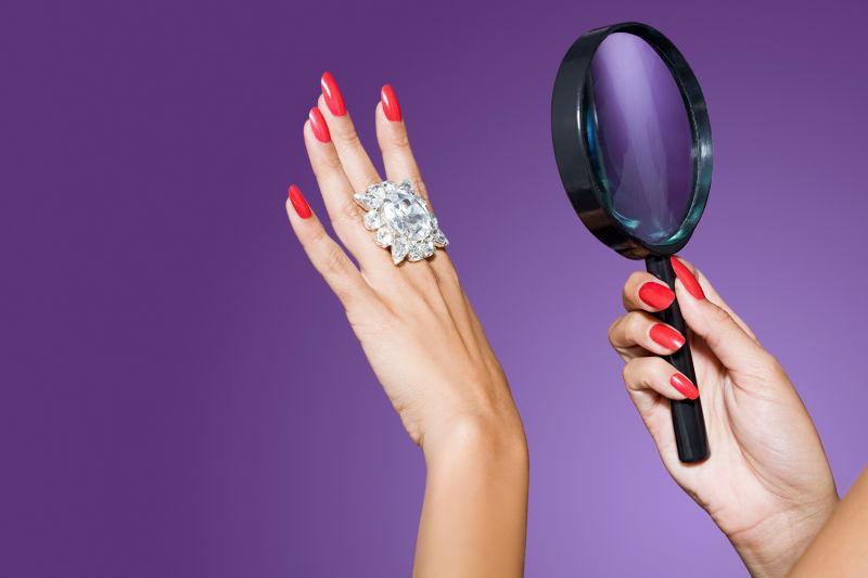 手拿放大镜看钻石戒指