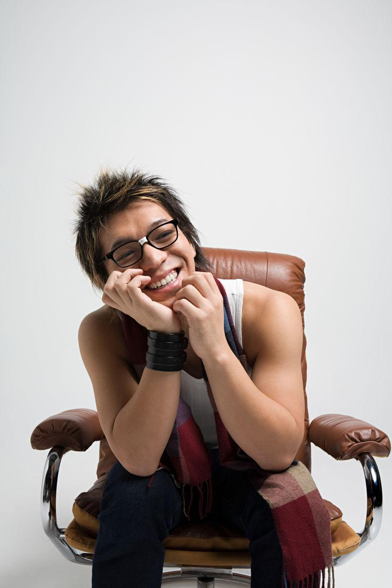白色背景下坐在棕色扶手椅上微笑的年轻亚裔男子
