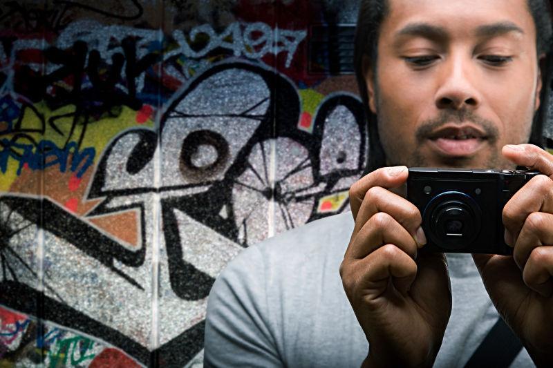 在涂鸦墙前面拿着照相机的男人