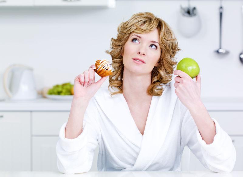 在健康食品和热量食品之间做选择的美女