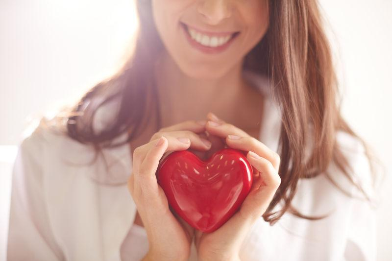 微笑的女子紧抱着红心