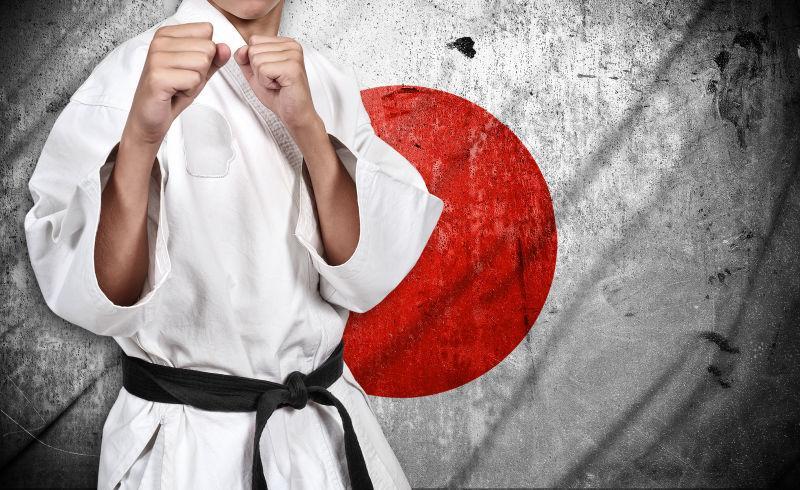 日本国旗背景下的白和服空手道战斗机
