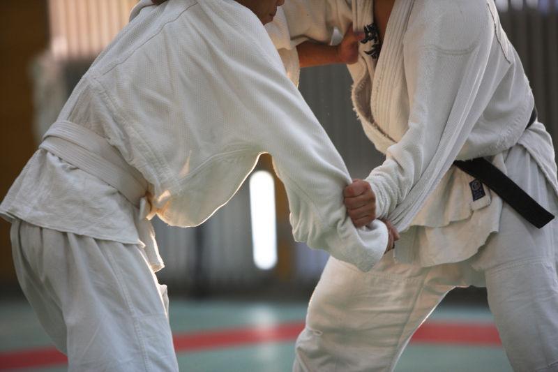 穿白色服饰的两人进行柔道运动