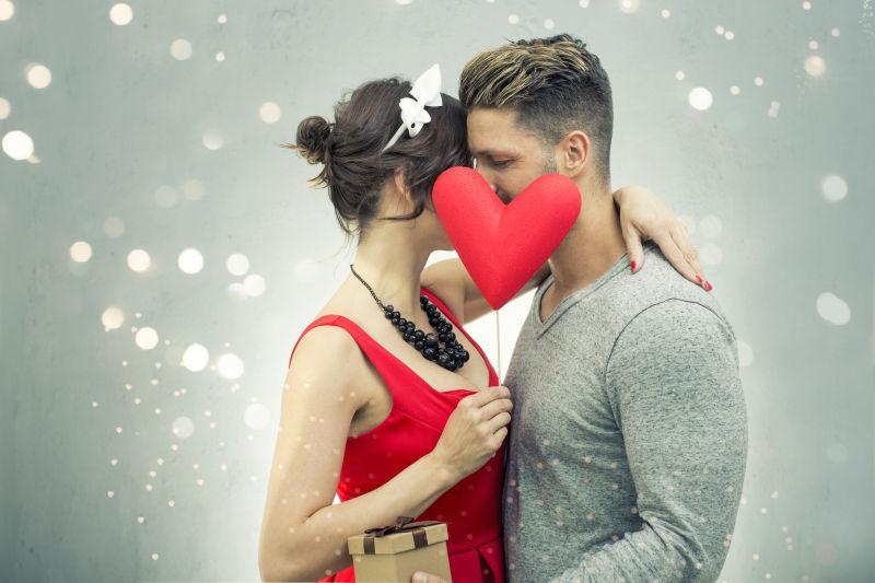 拿着红色心形接吻的夫妇