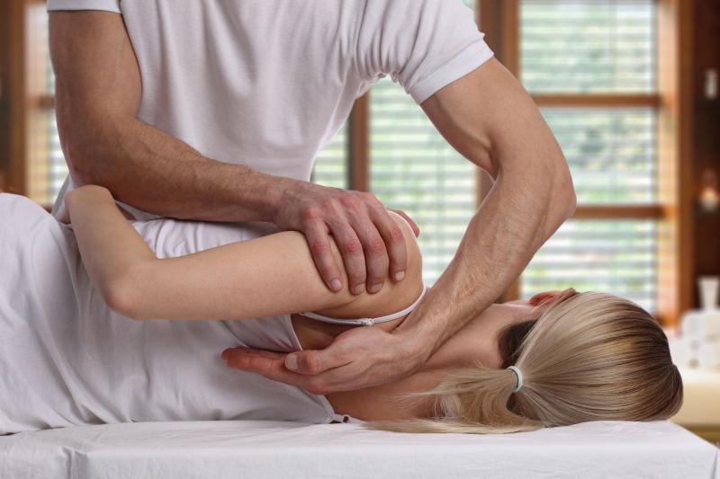 男性按摩师为女性矫正脊椎