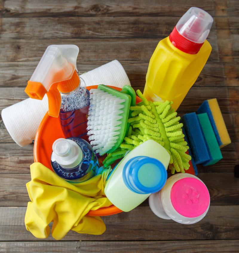 木材背景上带清洁用品的塑料桶