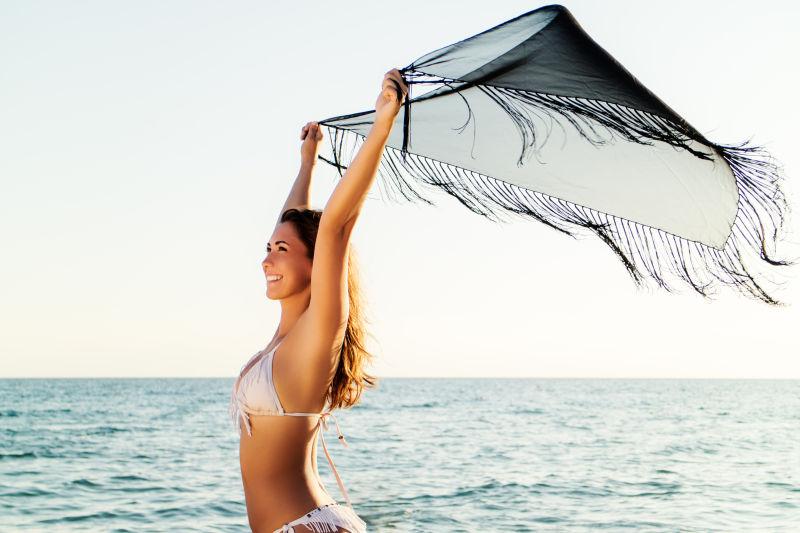 美女在海边拿着丝巾