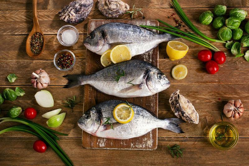 有香料和蔬菜的案板上的新鲜生鱼