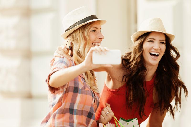 在用手机自拍的两个美女