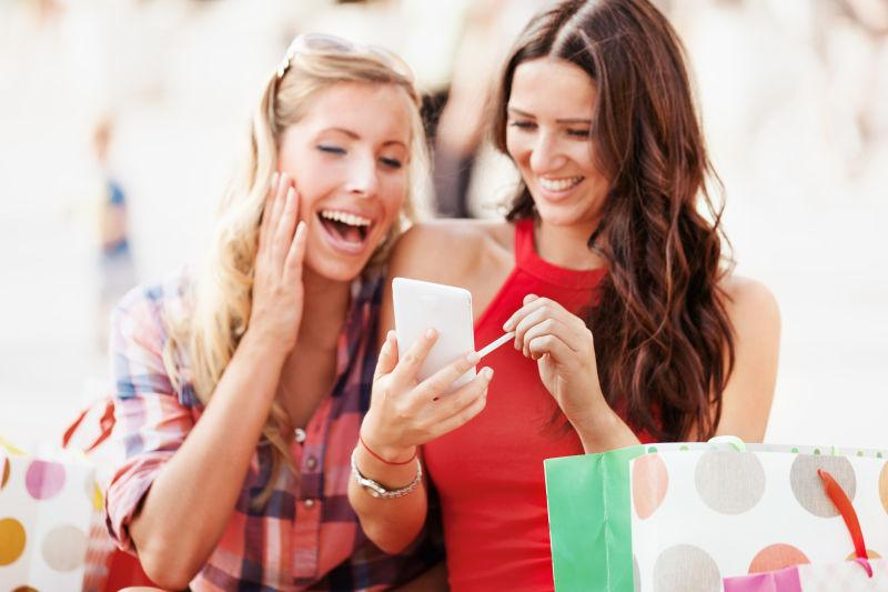 兴奋的拎着购物袋的美女用手机在聊天