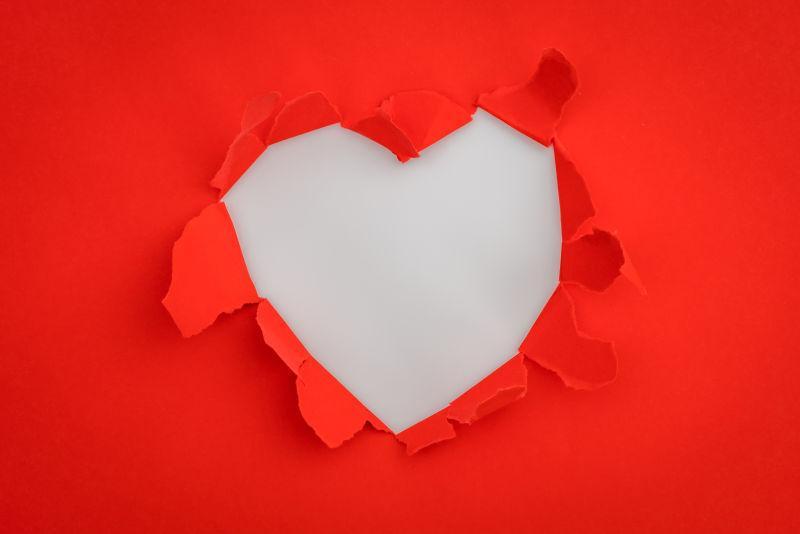 灰色桌上被撕开成心形的红纸