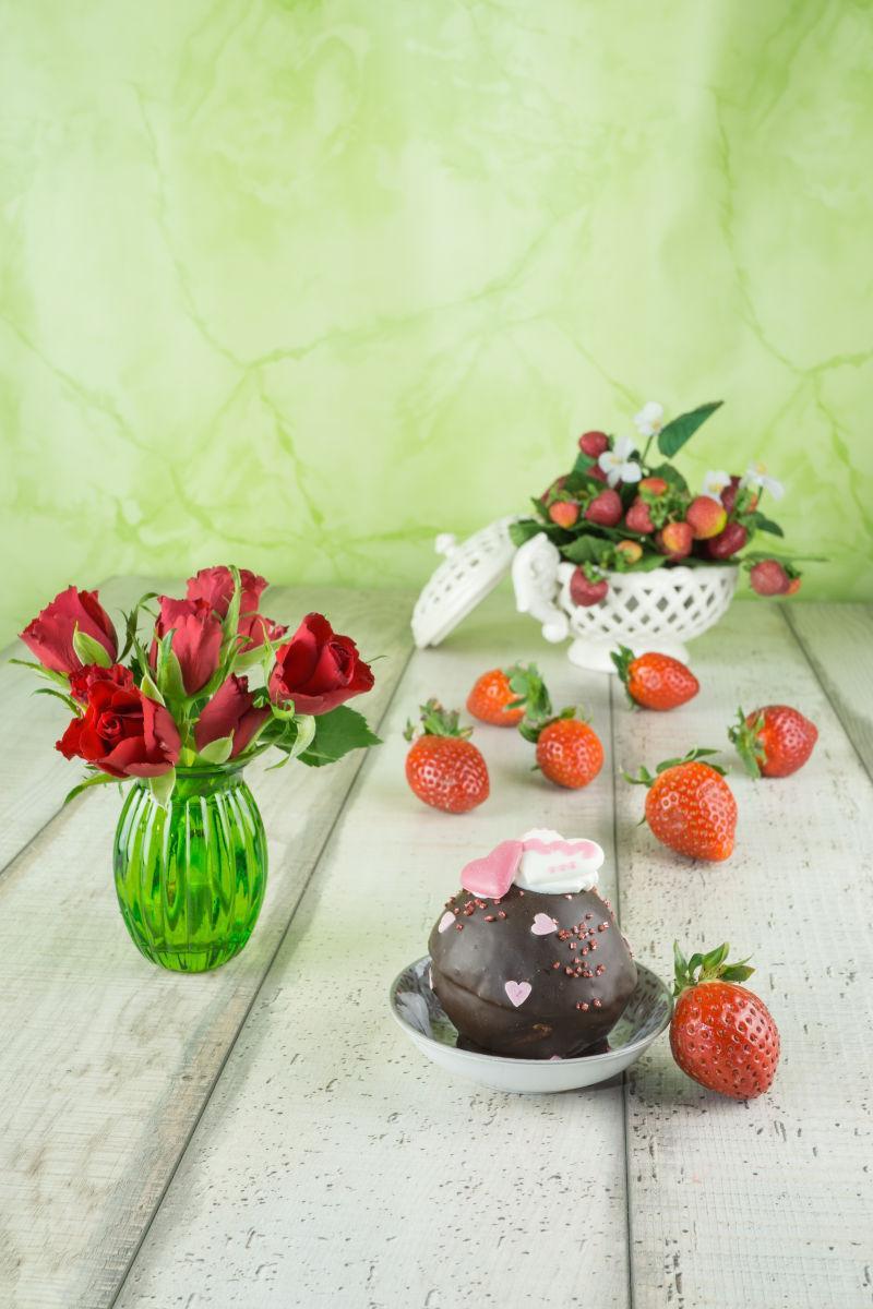 木制桌面上的巧克力甜点草莓和鲜花装饰