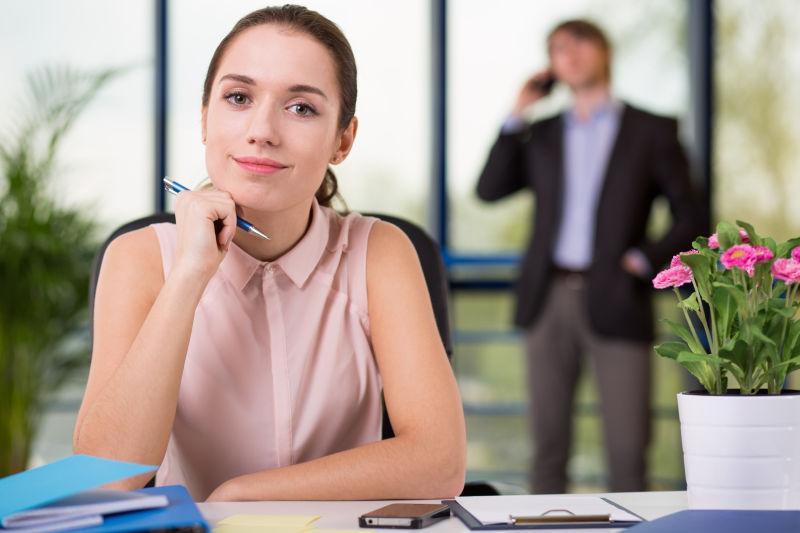 办公室背景中拿着笔发呆的年轻女秘书