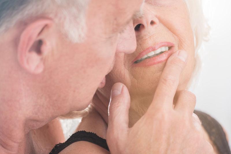高龄男人抚摸着老伴的嘴唇