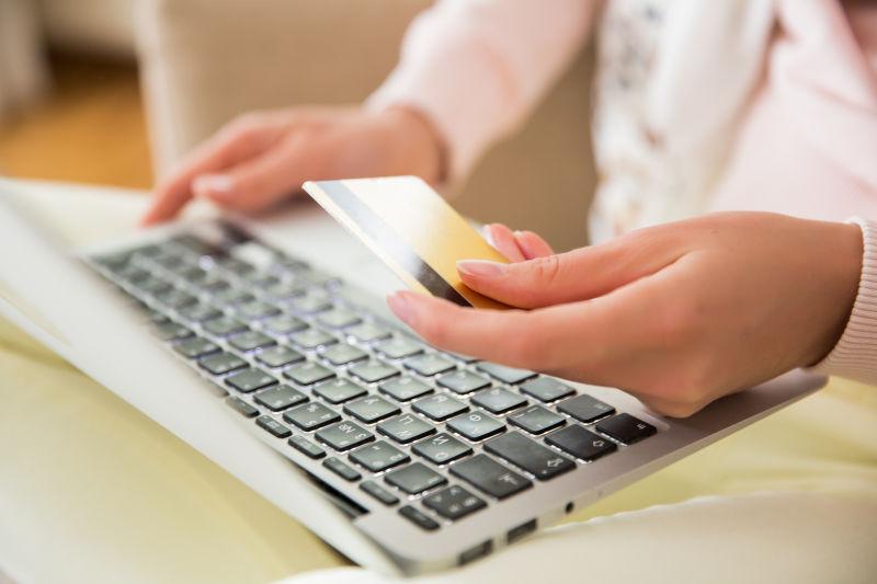 快乐的成年妇女坐在家里的沙发上带着笔记本电脑和信用卡