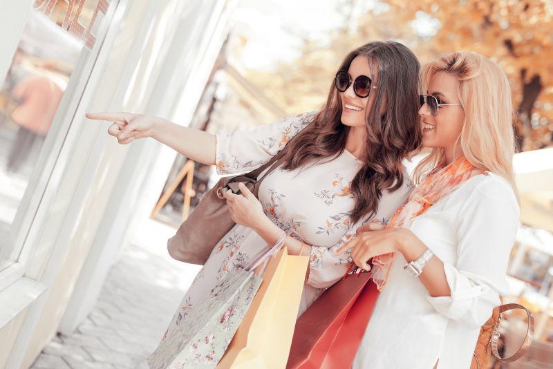 年轻女人提着购物袋指着商店橱窗