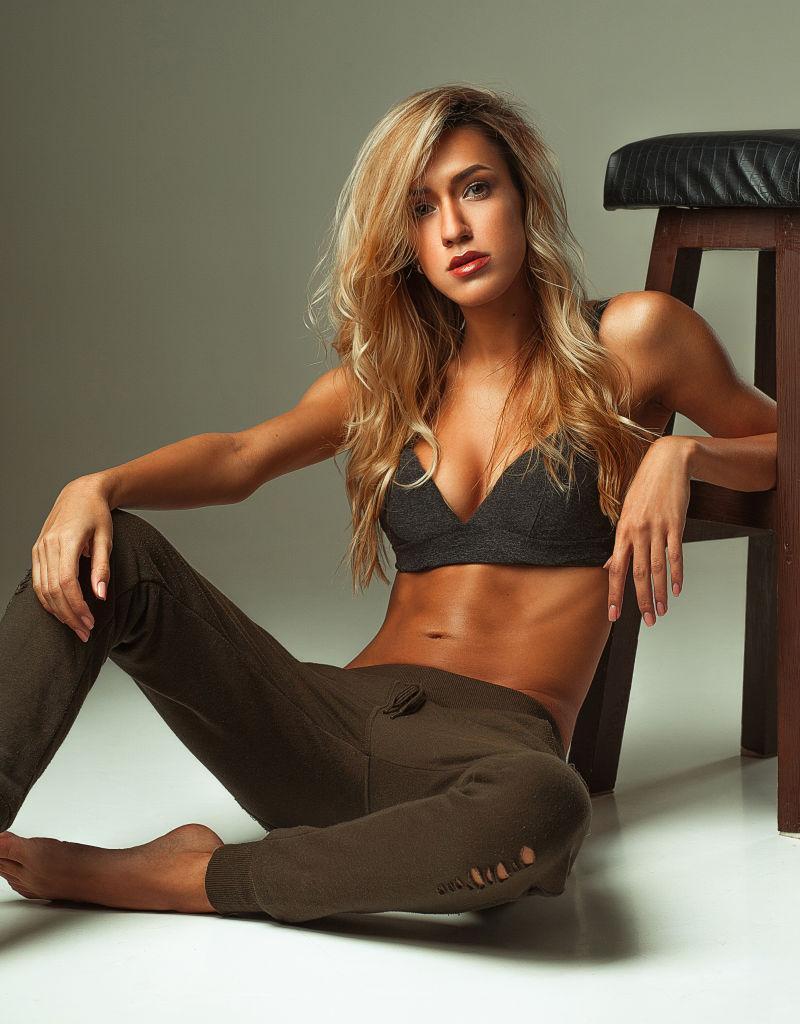 晒黑的女孩在胸罩顶部和裤子坐在地板上